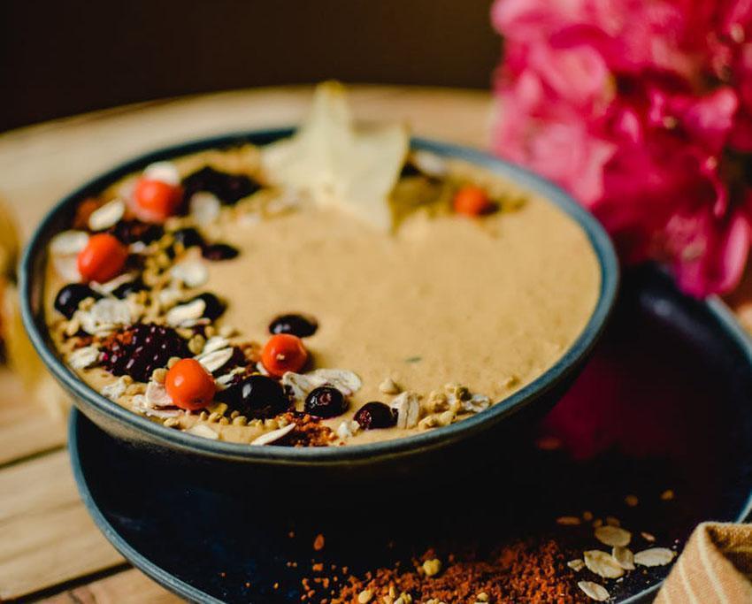Le Smoothie Bowl au beurre de cacahuète, graines concassées, amandes effilées, casis et mures